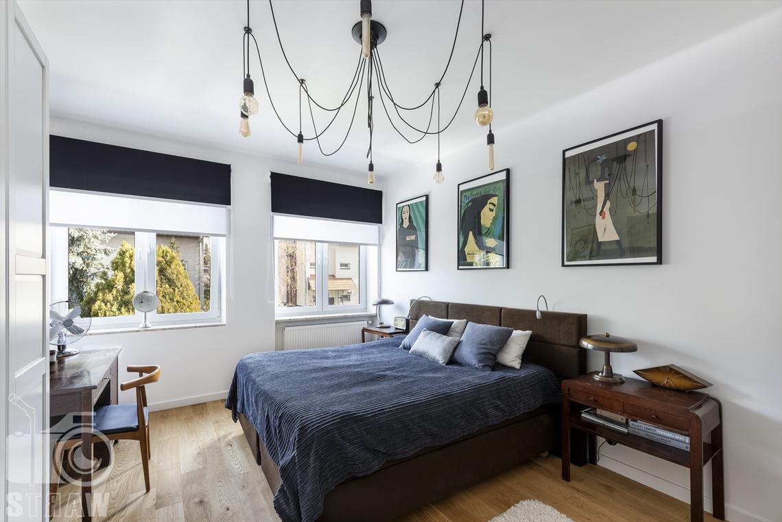 Zdjęcia nieruchomości na sprzedaż, sypialnia z łóżkiem małżeńskim i dużym żyrandolem.