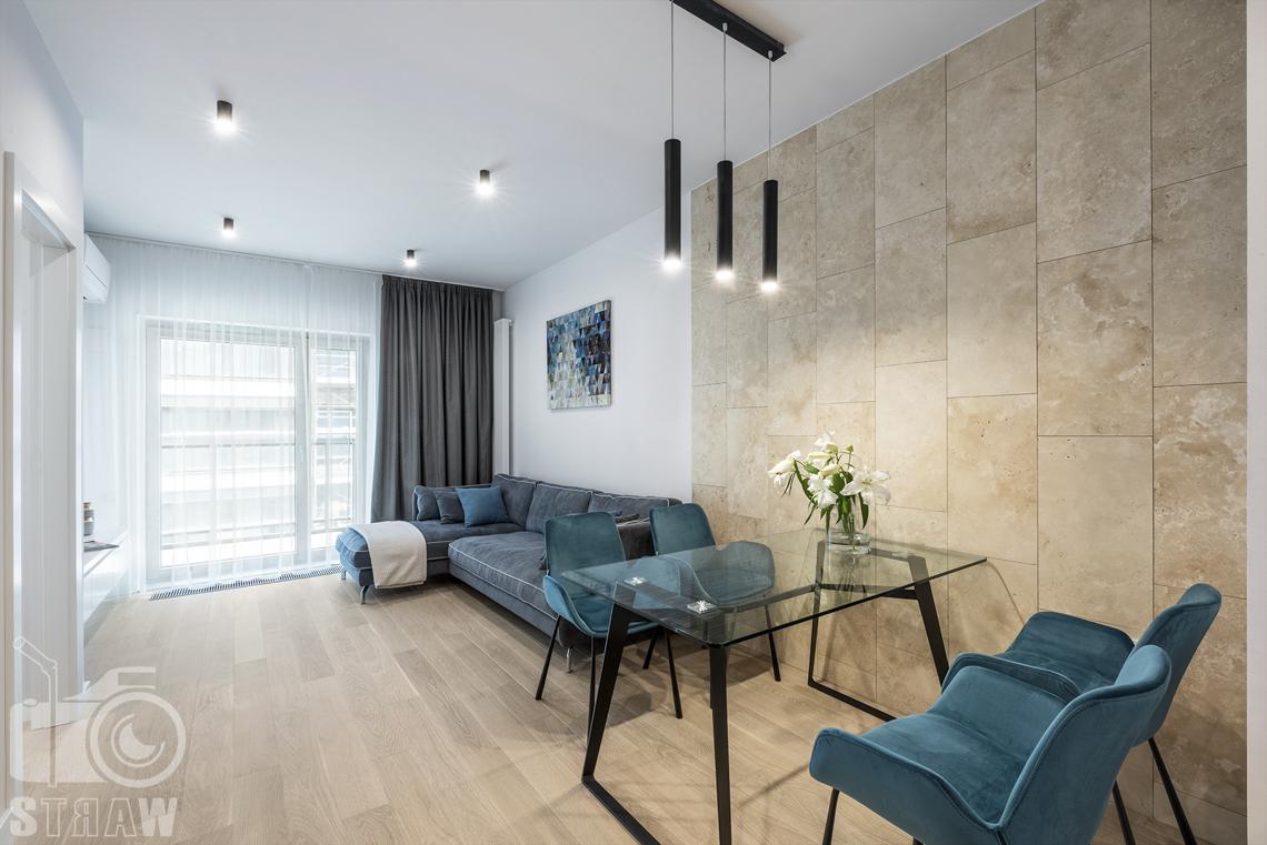 Fotograf wnętrz i zdjęcia nieruchomości na wynajem, salon i jadalnia w jednym, krzesła i sofa w tonacji niebieskiej, żyrandol i marmurowa ściana.