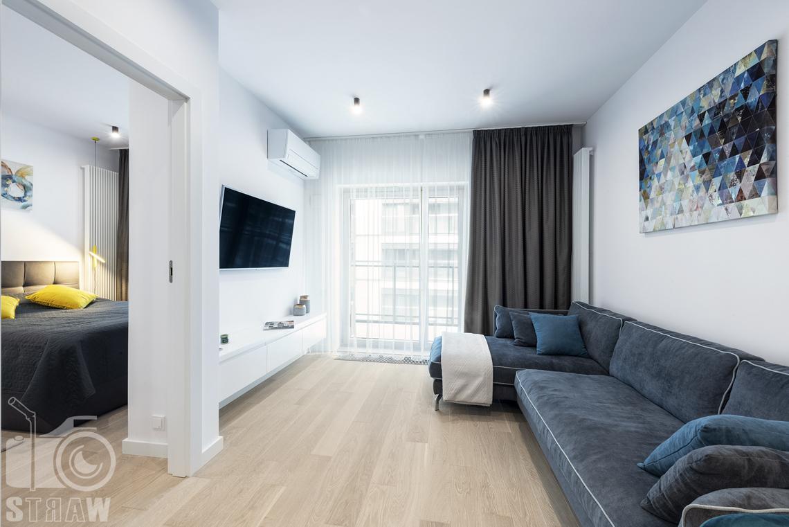 Fotograf wnętrz i zdjęcia nieruchomości na wynajem, salon z sofą i telewizorem oraz sypialnia.