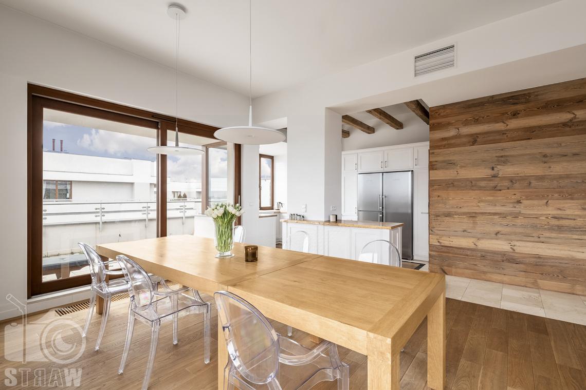 Fotografia nieruchomości na sprzedaż, zdjęcia dla agencji nieruchomości, drewniany stół w jadalni z przeźroczystymi krzesłami, widok na taras.
