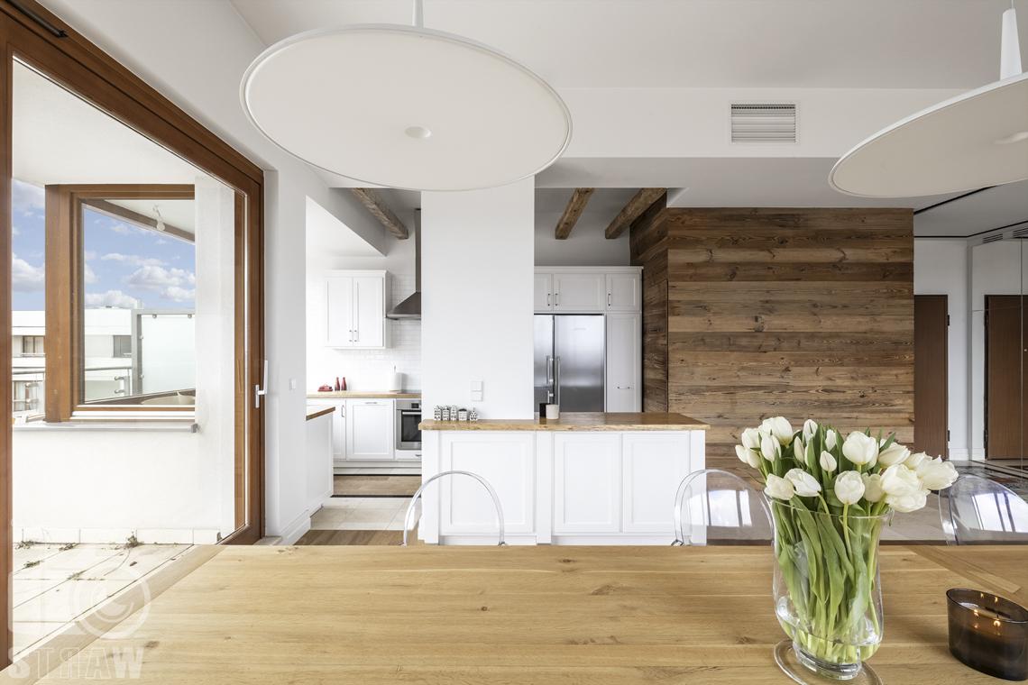 Fotografia nieruchomości na sprzedaż, zdjęcia dla agencji nieruchomości, stół w jadalni z wazonem tulipanów, lampy nad stołem.