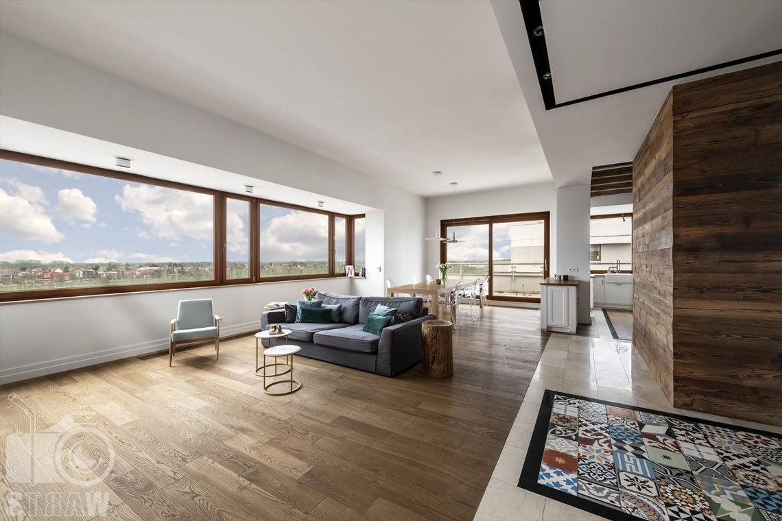 Fotografia nieruchomości na sprzedaż, zdjęcia dla agencji nieruchomości, salon z drewnianym parkietem, fotel, sofa, mozaika w przedpokoju.