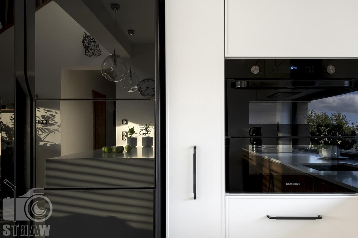Fotografia wnętrz dla producenta mebli kuchennych, odbicia wnętrza w czarnym połyskującym agd.