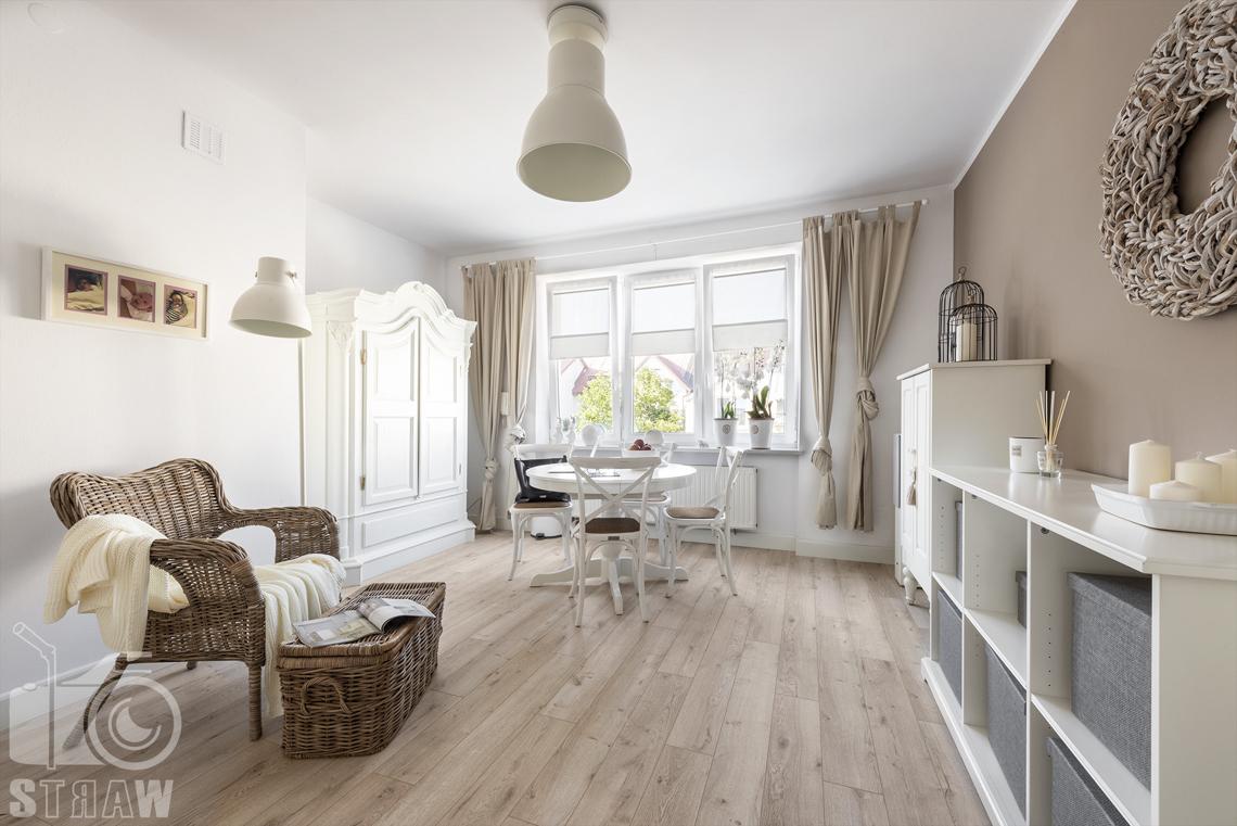 Fotografia wnętrz nieruchomości na sprzedaż Warszawa, gabinet z drewnianą podłogą, wiklinowym fotelem, okrągłym stołem i białą komodą.