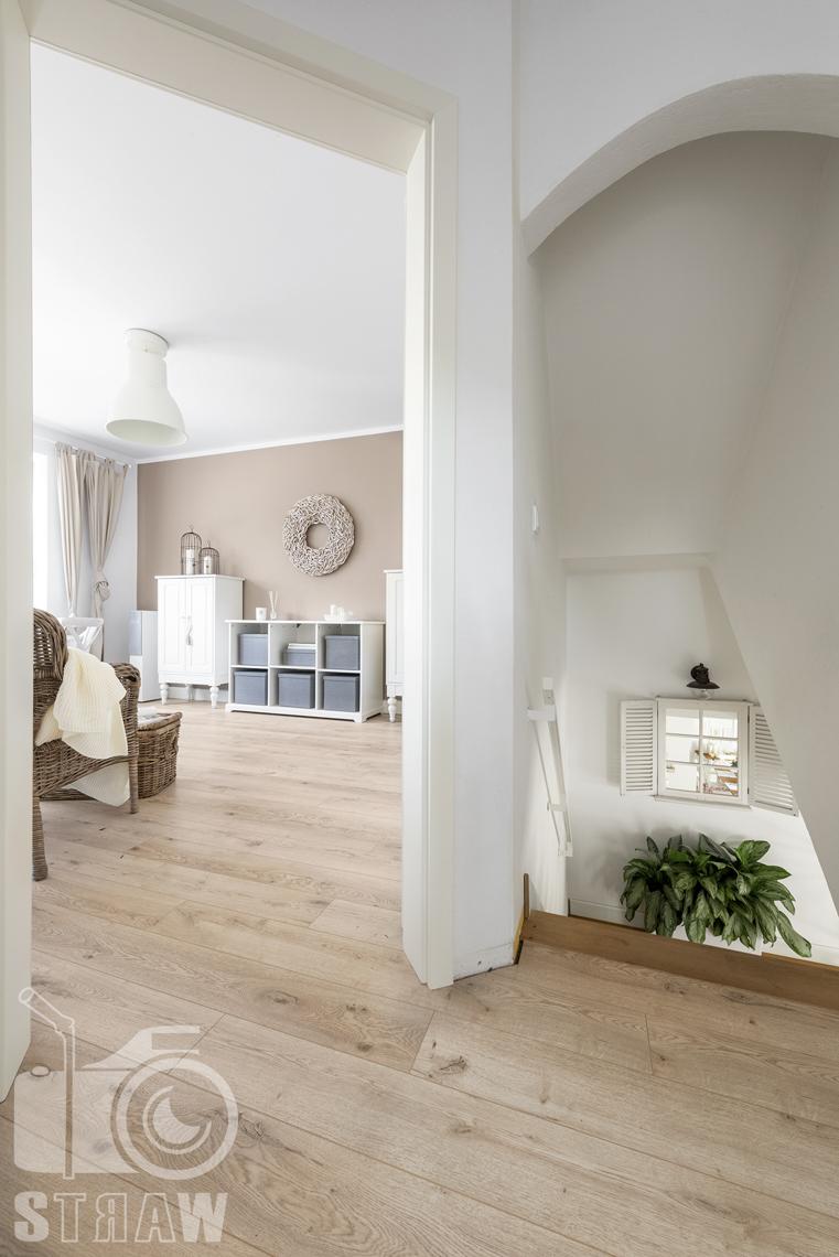 Fotografia wnętrz nieruchomości na sprzedaż Warszawa, wejście do gabinetu, widok na białe szafki oraz na schody z lustrem w kształcie okna.