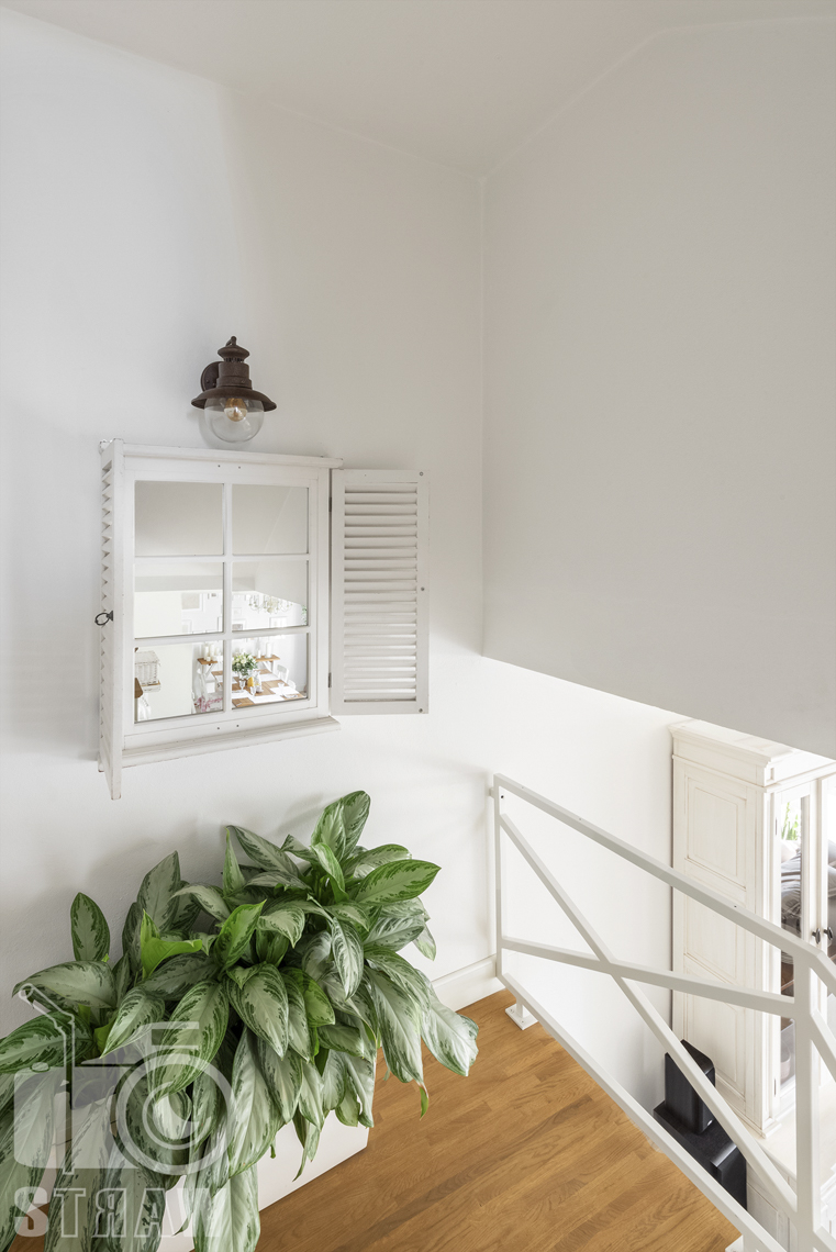 Fotografia wnętrz nieruchomości na sprzedaż Warszawa, półpiętro na schodach z lustrem w postaci okienka z okiennicami.