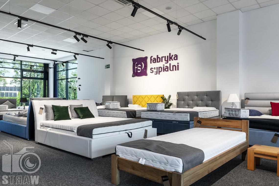 Fotografia wnętrz komercyjnych, zdjęcia sklepu meblowego fabryka sypialni, na pierwszym planie pojedyncze łóżko drewniane.