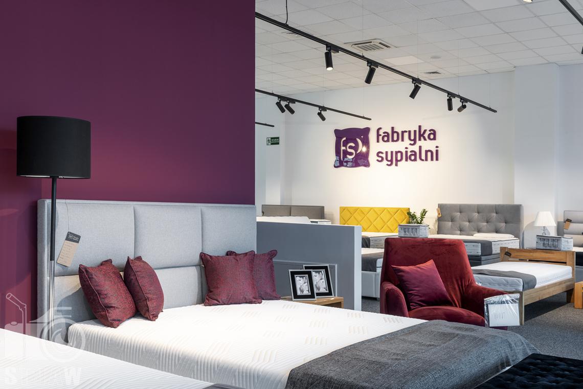 Fotografia wnętrz komercyjnych, zdjęcia sklepu meblowego Fabryka Sypialni w Łodzi, łóżko z szaryn zagłówkiem i bordowe poduszki.