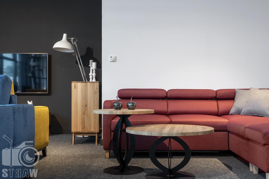 Fotografia wnętrz komercyjnych, zdjęcia showroomu meblowego, na zdjęciu wda stoliki kawowe z drewnianymi blatami oraz łososiowa sofa, narożnik.