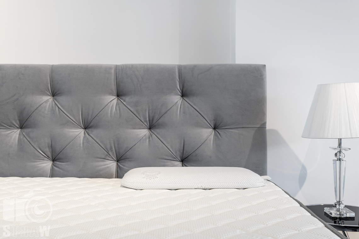 Fotografia wnętrz komercyjnych, zdjęcia sklepu meblowego fabryka sypialni w łodzi, łóżko z szarym zagłówkiem i biała lampka nocna.