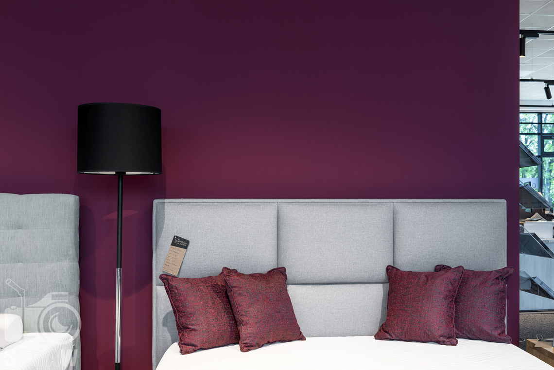 Fotografia wnętrz komercyjnych, zdjęcia sklepu meblowego Fabryka Sypialni w Łodzi, łóżka z szarymi zagłówkami i lampa z czarnym abażurem.