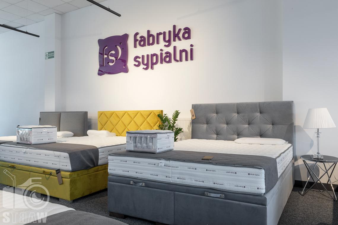 Fotografia wnętrz komercyjnych, zdjęcia sklepu meblowego łóżka z zagłówkami i stolik z lampką nocną.