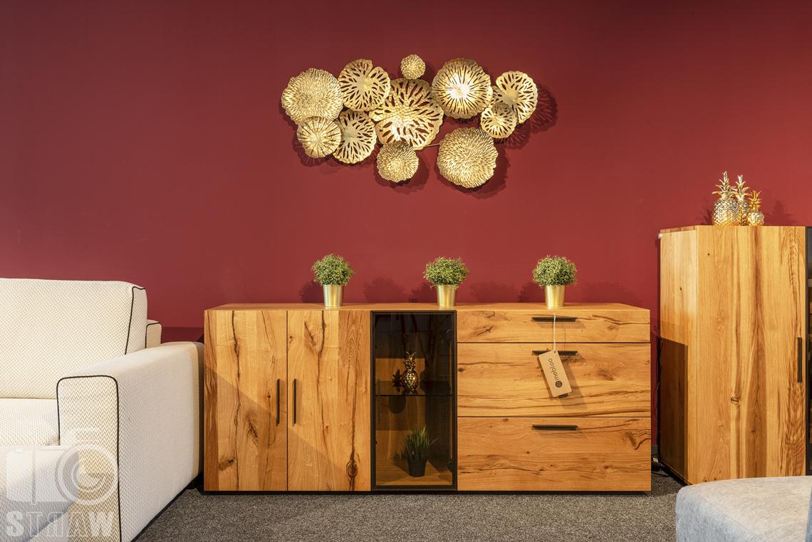 Fotografia wnętrz komercyjnych, zdjęcia showroomu meblowego, na zdjęciu drewniana komoda na tle czerwonej ściany.