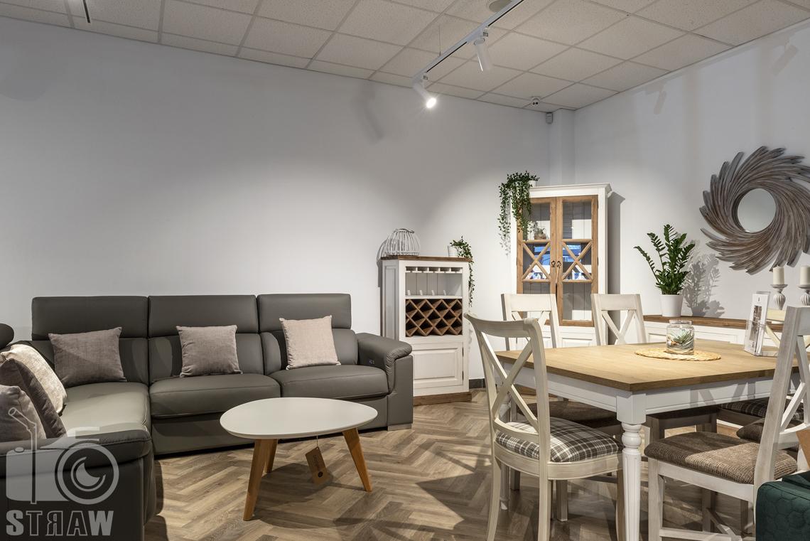 Fotografia wnętrz komercyjnych, zdjęcia showroomu meblowego, na zdjęciu drewniany komplet kuchenny oraz beżowa sofa skórzana.