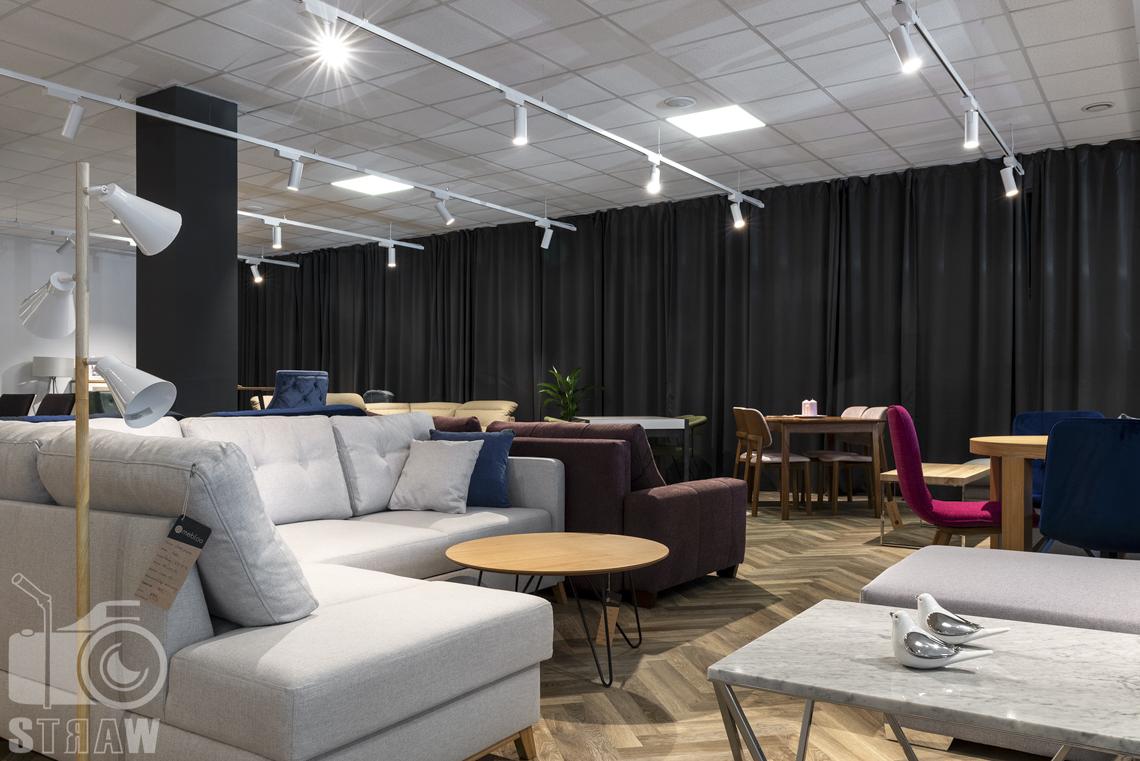 Fotografia wnętrz komercyjnych, zdjęcia showroomu meblowego, na pierwszym planie zdjęcia marmurkowe stoliki kawowe oraz szara sofa narożnik.