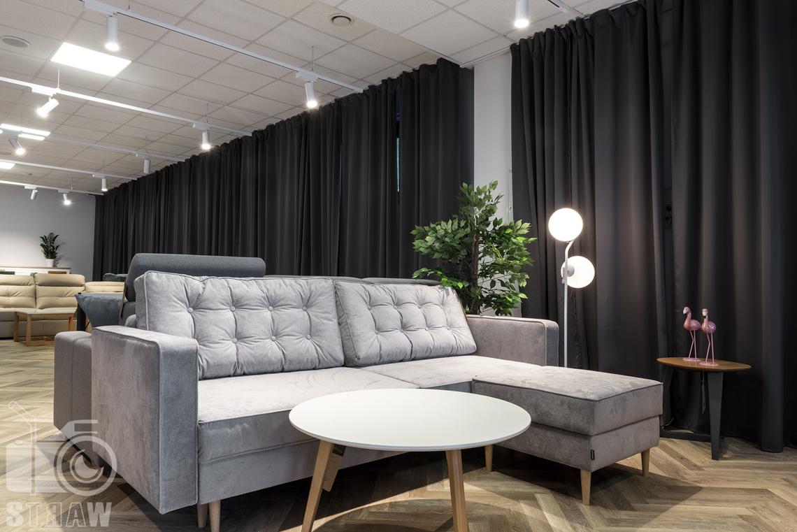 Fotografia wnętrz komercyjnych, zdjęcia showroomu meblowego na zdjęciu szara pikowana sofa i okrągły stolik kawowy.