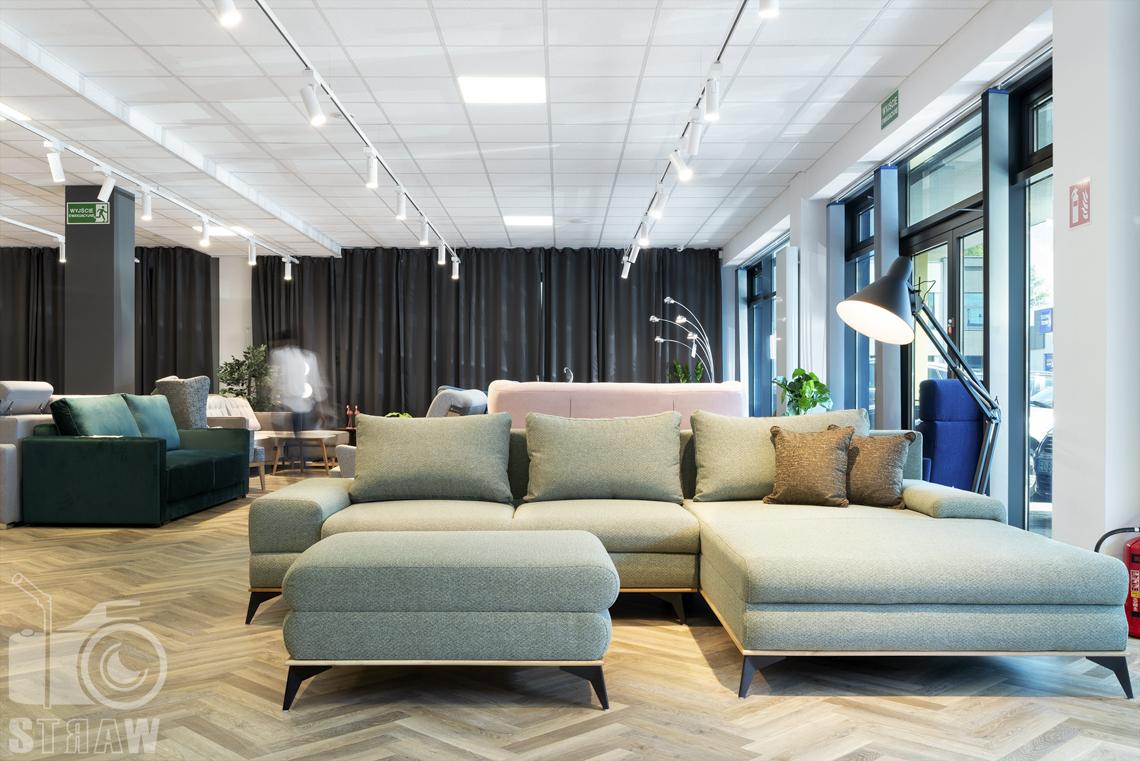 Fotografia wnętrz komercyjnych, zdjęcia showroomu meblowego, na zdjęciu sofa narożnik z miejscem do leżenia.