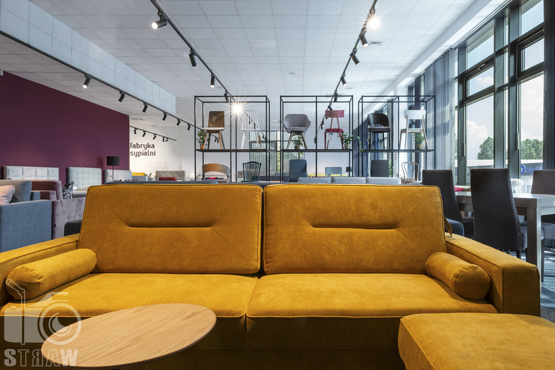 Fotografia wnętrz komercyjnych, zdjęcia showroomu meblowego z żółtą sofą i drewnianym okrągłym stolikiem kawowym.