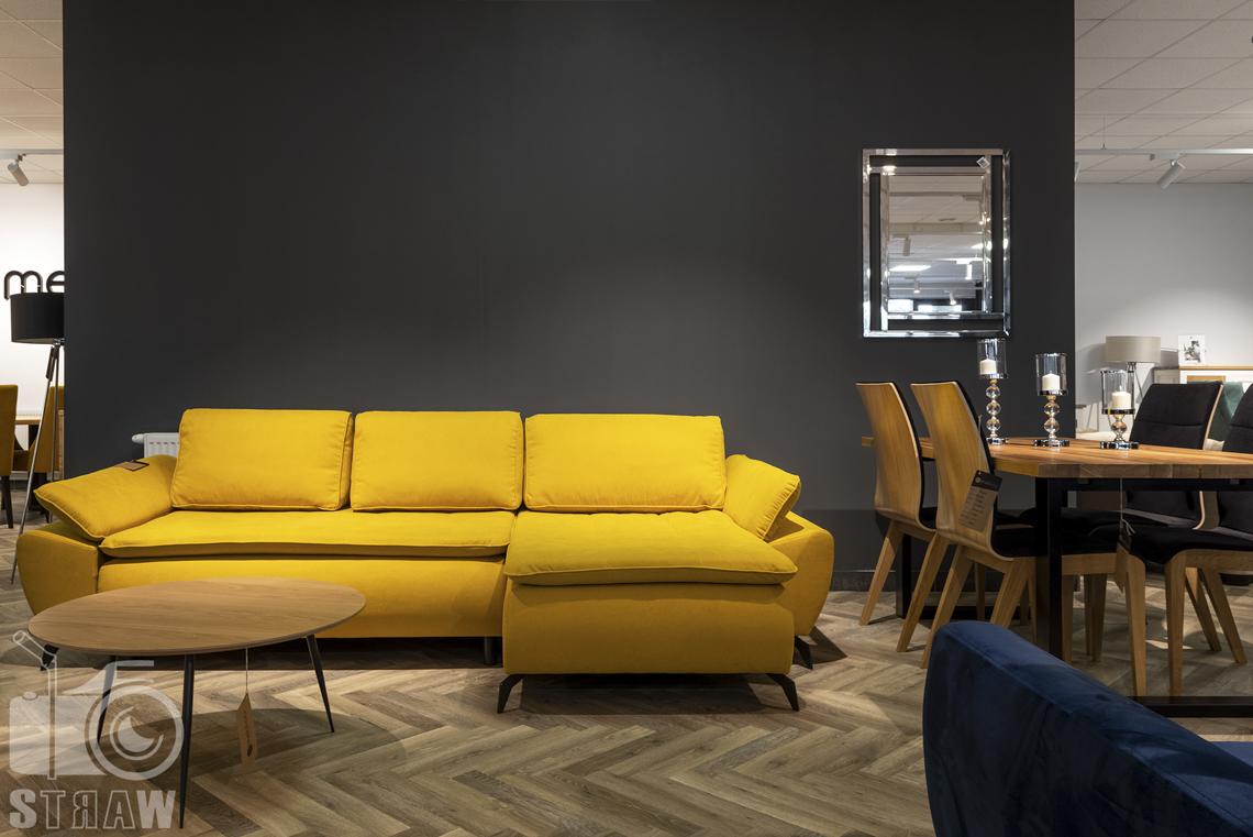Fotografia wnętrz komercyjnych, zdjęcia showroomu meblowego Mebloo, na zdjęciu żółta sofa, okrągły stolik kawowy i stół do jadalni.