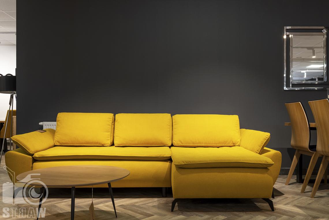 Fotografia wnętrz komercyjnych, zdjęcia showroomu meblowego, na zdjęciu żółta sofa i okrągły drewniany stolik kawowy.