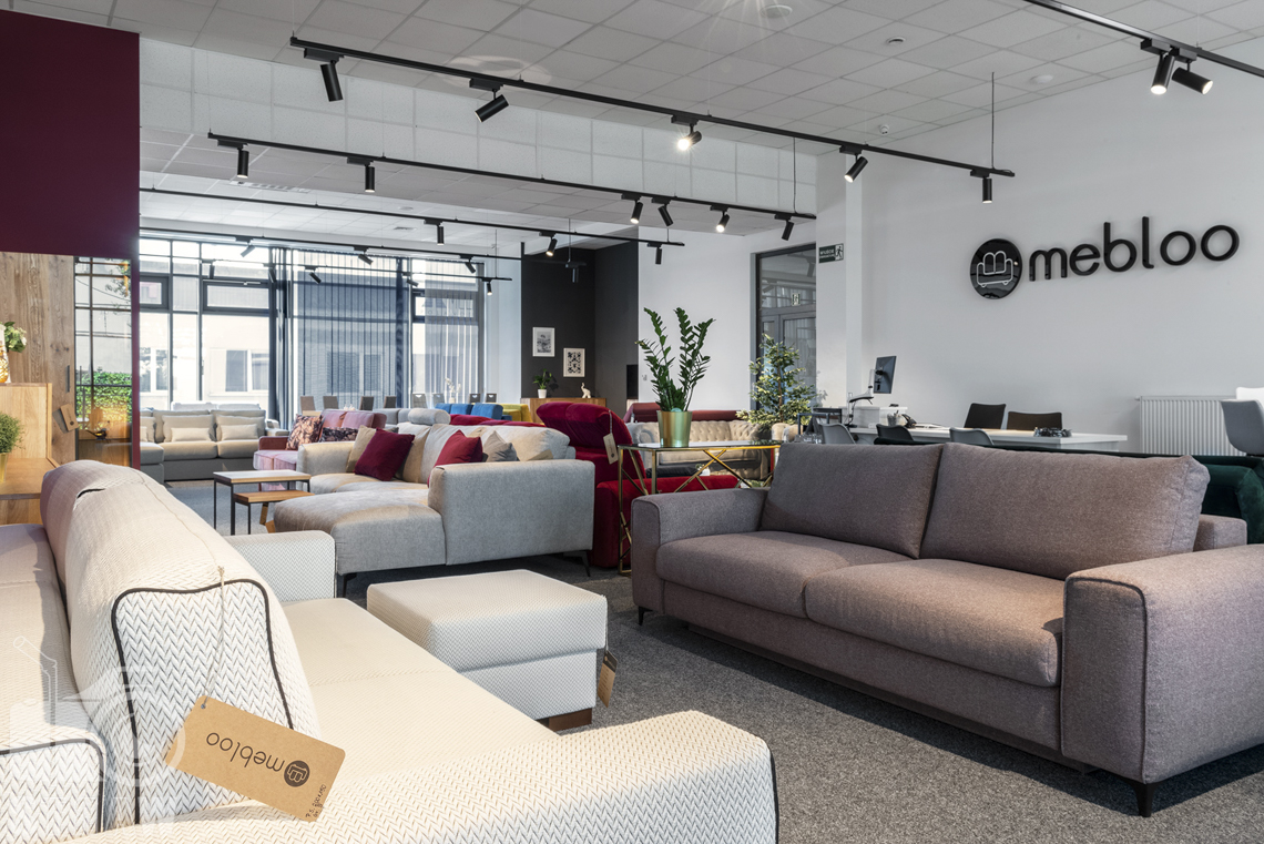 Fotografia wnętrz komercyjnych, zdjęcia showroomu meblowego z sofami białą i beżową.