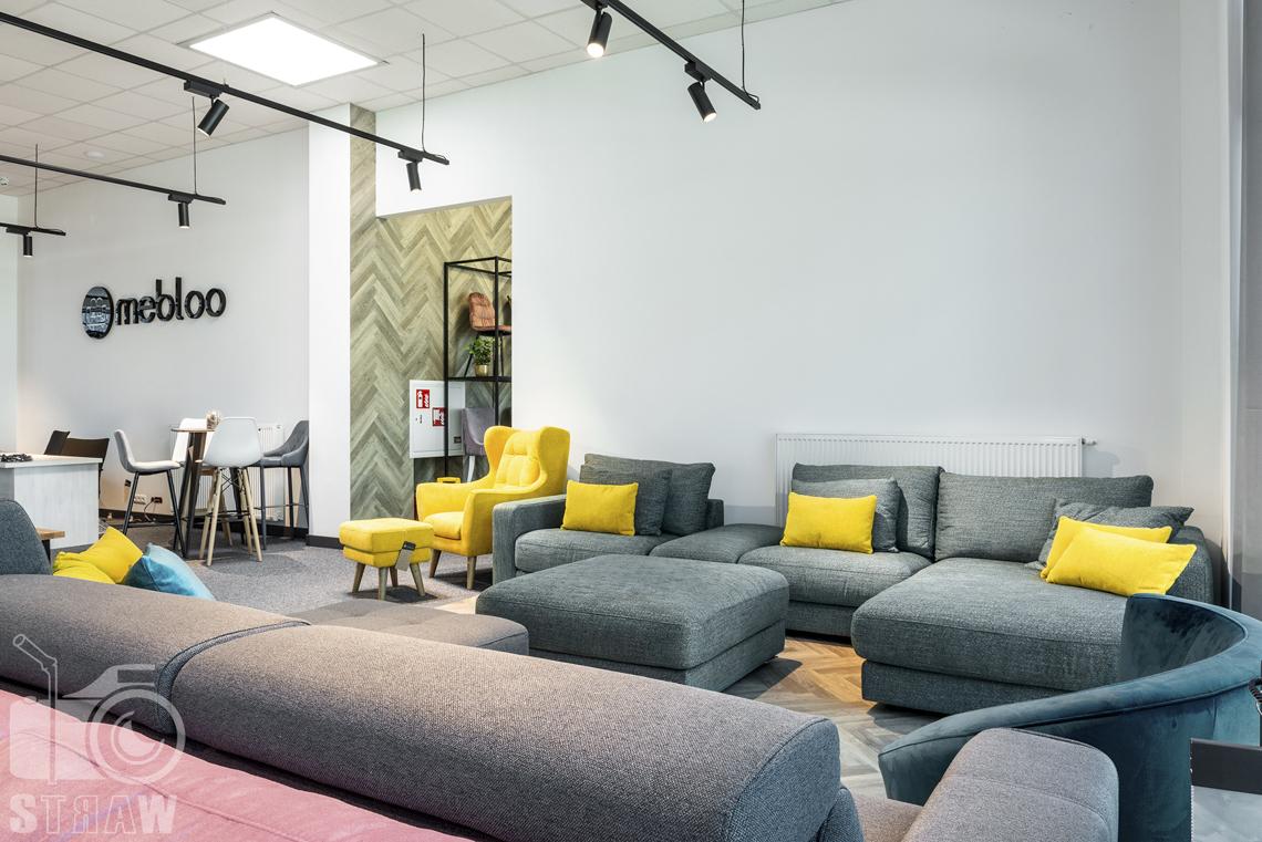 Fotografia wnętrz komercyjnych, zdjęcia showroomu meblowego Mebloo w Łodzi, na zdjęciu sofa narożnik w kolorze zieleni morskiej oraz żółty fotel.