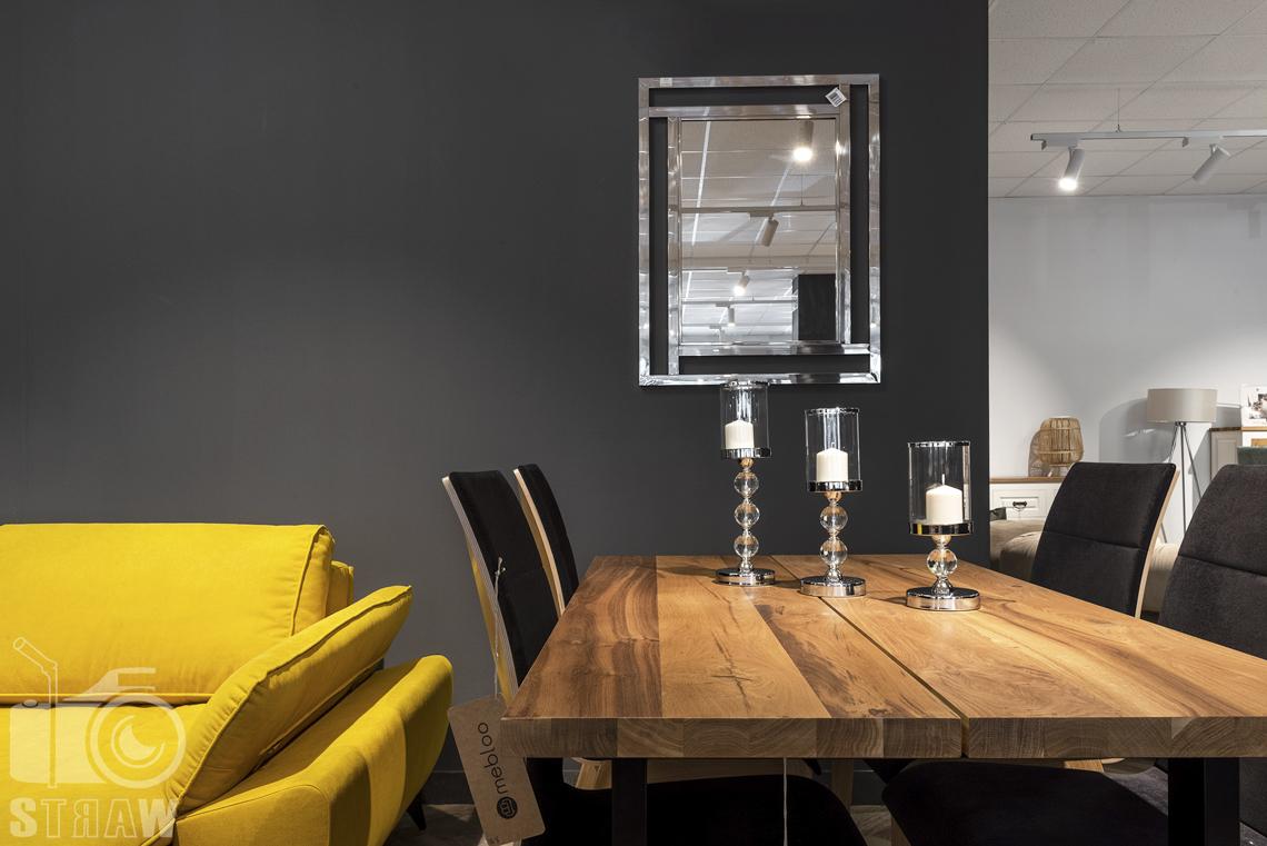 Fotografia wnętrz komercyjnych, zdjęcia sklepu meblowego, drewniany stół, świeczniki i lustro.