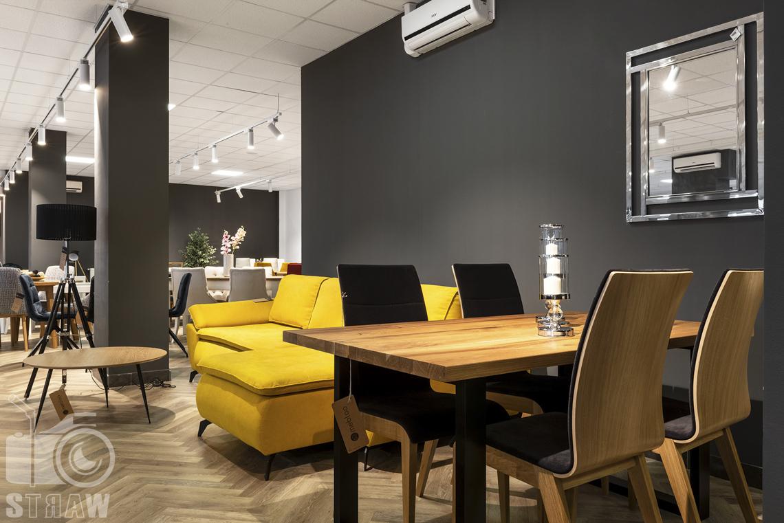 Fotografia wnętrz komercyjnych, zdjęcia sklepu meblowego w Łodzi, stół i drewniane krzesła z czarnymi obiciami.