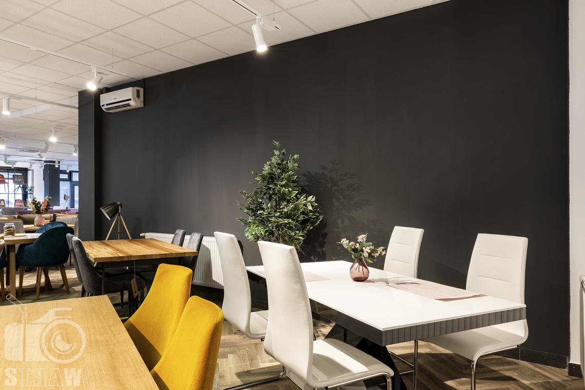 Fotografia wnętrz komercyjnych, zdjęcia białego stołu i białych krzeseł na tle ciemnej ściany w sklepie meblowym Mebloo w Łodzi.