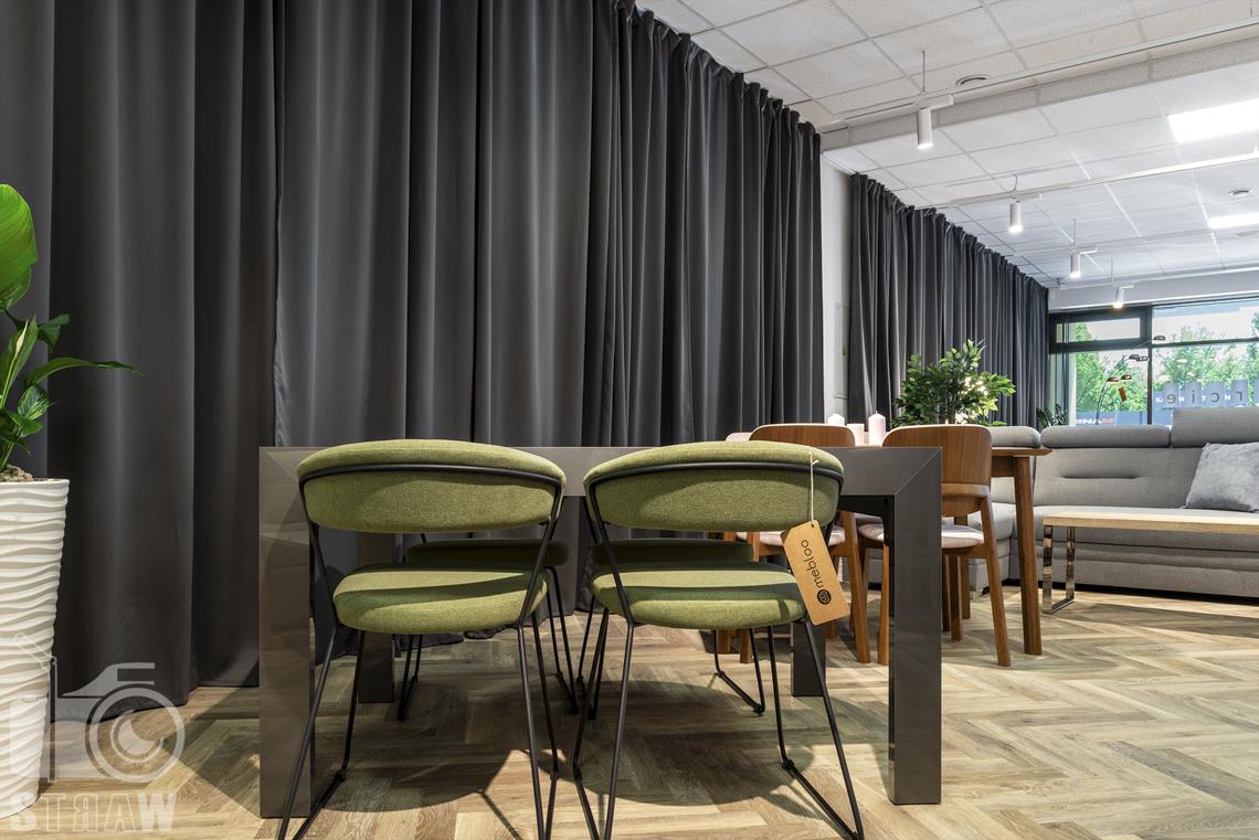 Fotografia wnętrz komercyjnych, zdjęcia zielonych krzeseł i szarego stołu na tle zasłon w sklepie meblowym Mebloo.