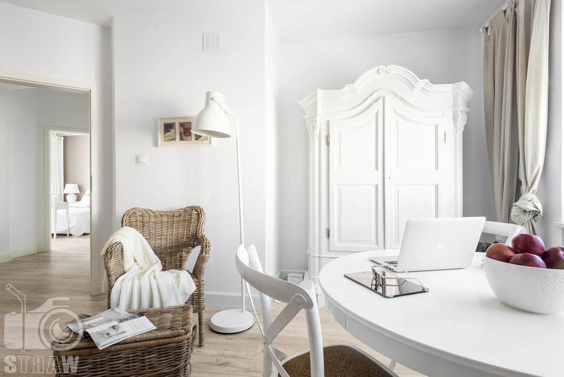 Fotografia wnętrz nieruchomości na sprzedaż Warszawa, gabinet z iałym okrągłym stołem, wiklinowym fotelem i białą komodą.