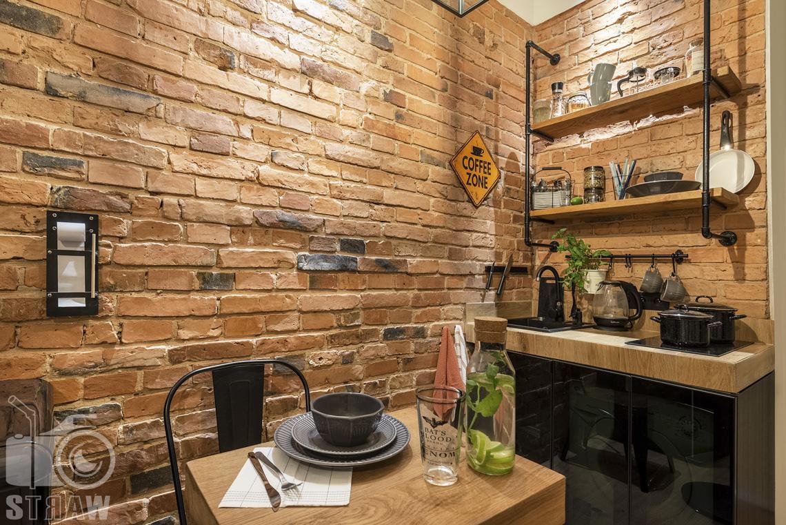 Fotografia booking, zdjęcia apartamentu na Pradze w Warszawie, w głębi część kuchenna, bliżej stolik kawowy z filiżanką i talerzykami.