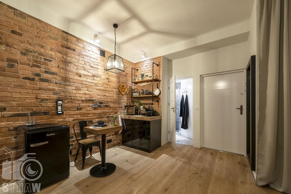 Fotografia booking, zdjęcia apartamentu, pokój z widokiem na część kuchenną i kawową, otwarte drzwi do łazienki z wieszakami na ręczniki i drzwi wejściowe do pokoju.