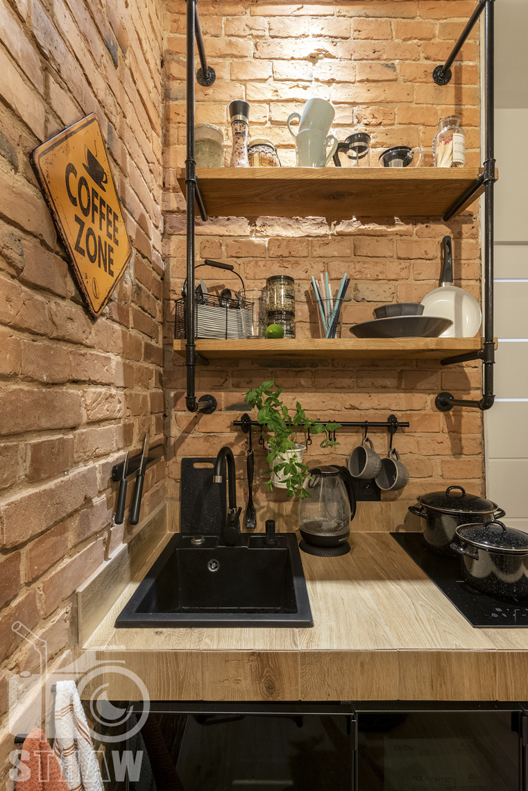 Fotografia booking, zdjęcia apartamentu, kuchnia z garnkami, zlewem, płytą grzewczą, półki z drobnymi elementami kuchennymi.