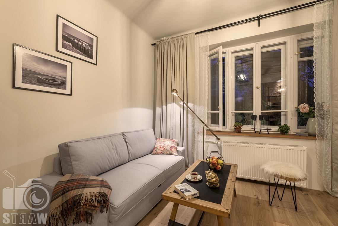 Fotografia booking, zdjęcia apartamentu na Pradze w Warszawie, część pokoju wypoczynkowego z oknem, sofą i dużym stołem, na ścianie dwa obrazy.