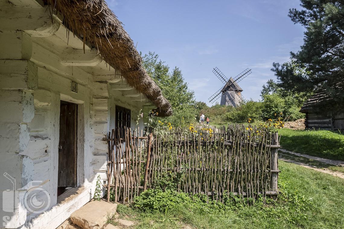 Fotografia architektury, zdjęcia budynków w skansenie wsi w Kielcach, chata wiejska kryta słomą, bielona, mały ogródek, a dalej wiatrak.
