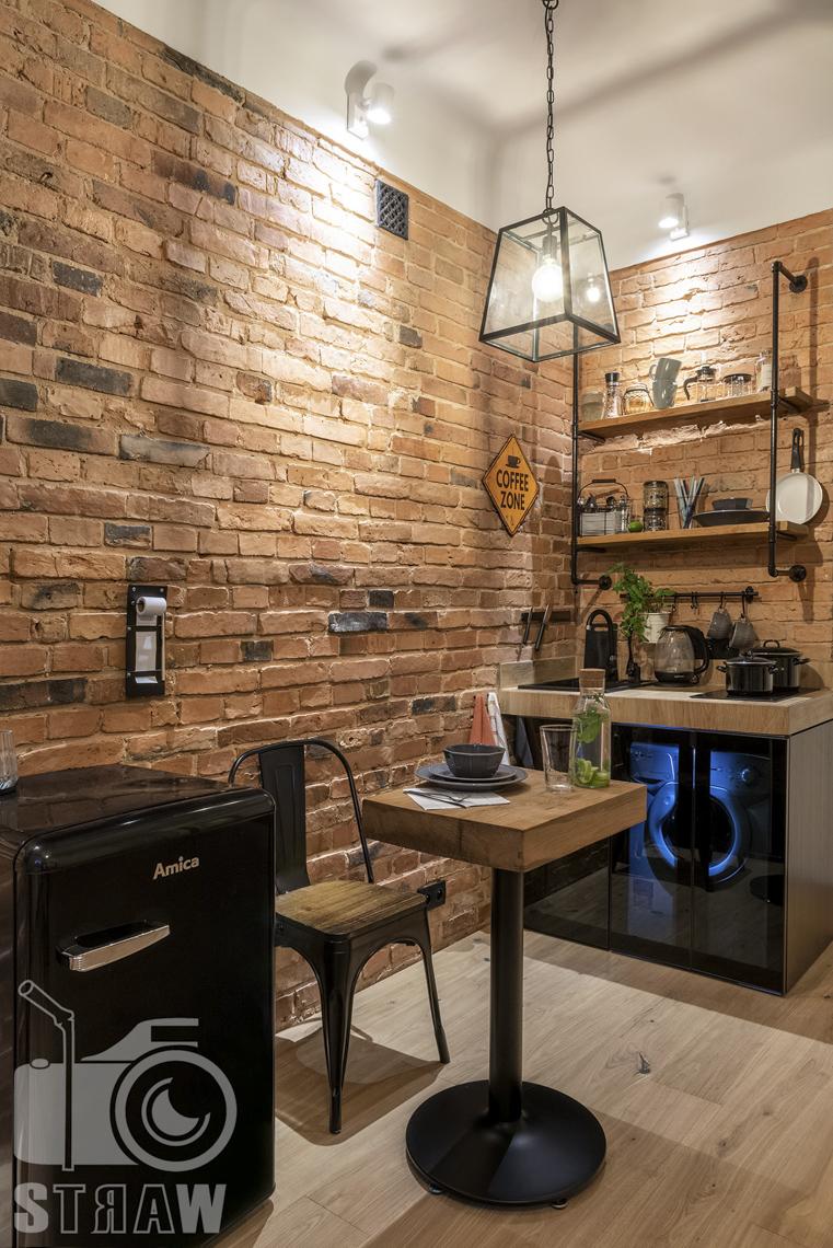Fotografia booking, zdjęcia apartamentu, kącik kawowy w pokoju wypoczynkowym, półki, stolik krzesło, lampa wisząca.