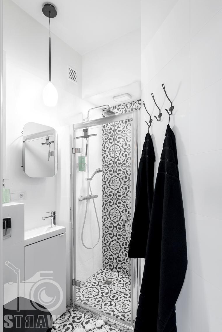 Fotografia booking, zdjęcia apartamentu, łazienka z kabiną prysznicową, wieszaki z ręcznikami, umywalka i lustro.