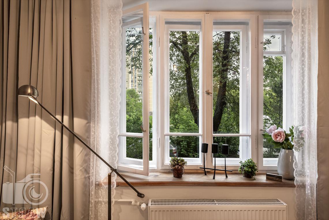 Fotografia booking, zdjęcia apartamentu, Okno z widokiem na drzewa, kaloryfer, lampka.