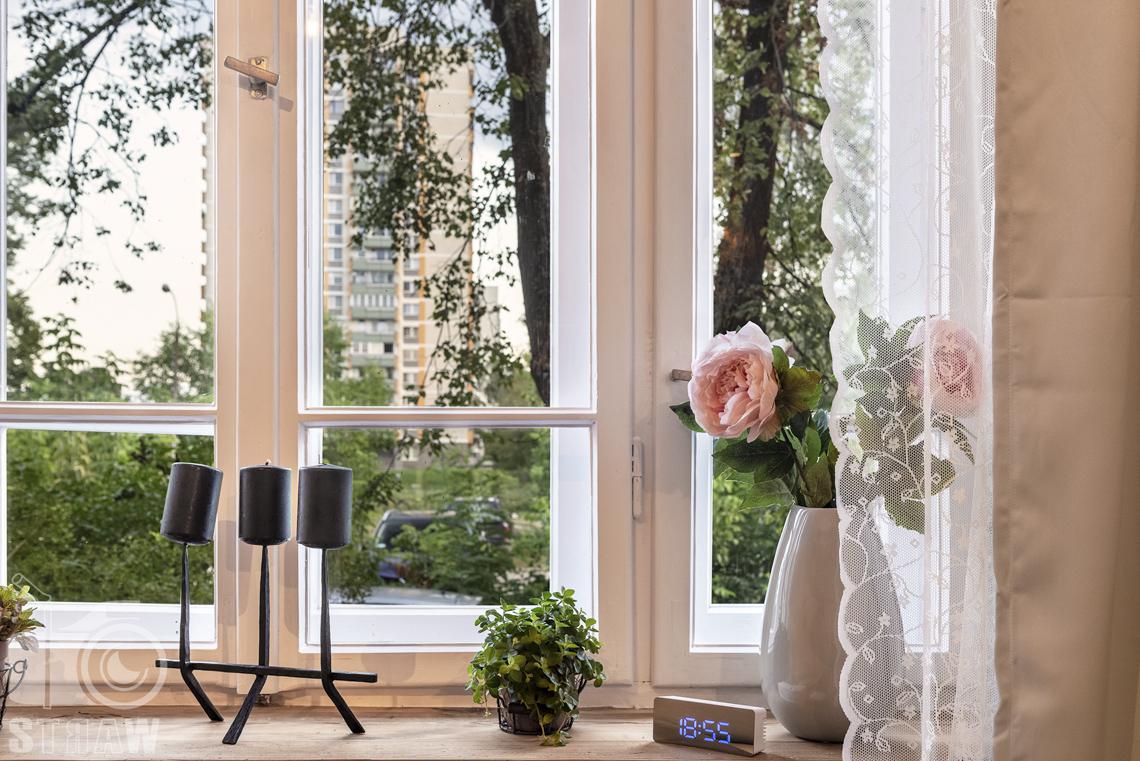 Fotografia booking, zdjęcia apartamentu, Okno z widokiem, na oknie dzban z kwiatami, świecznik, kwiaty doniczkowe, zegar elektroniczny.