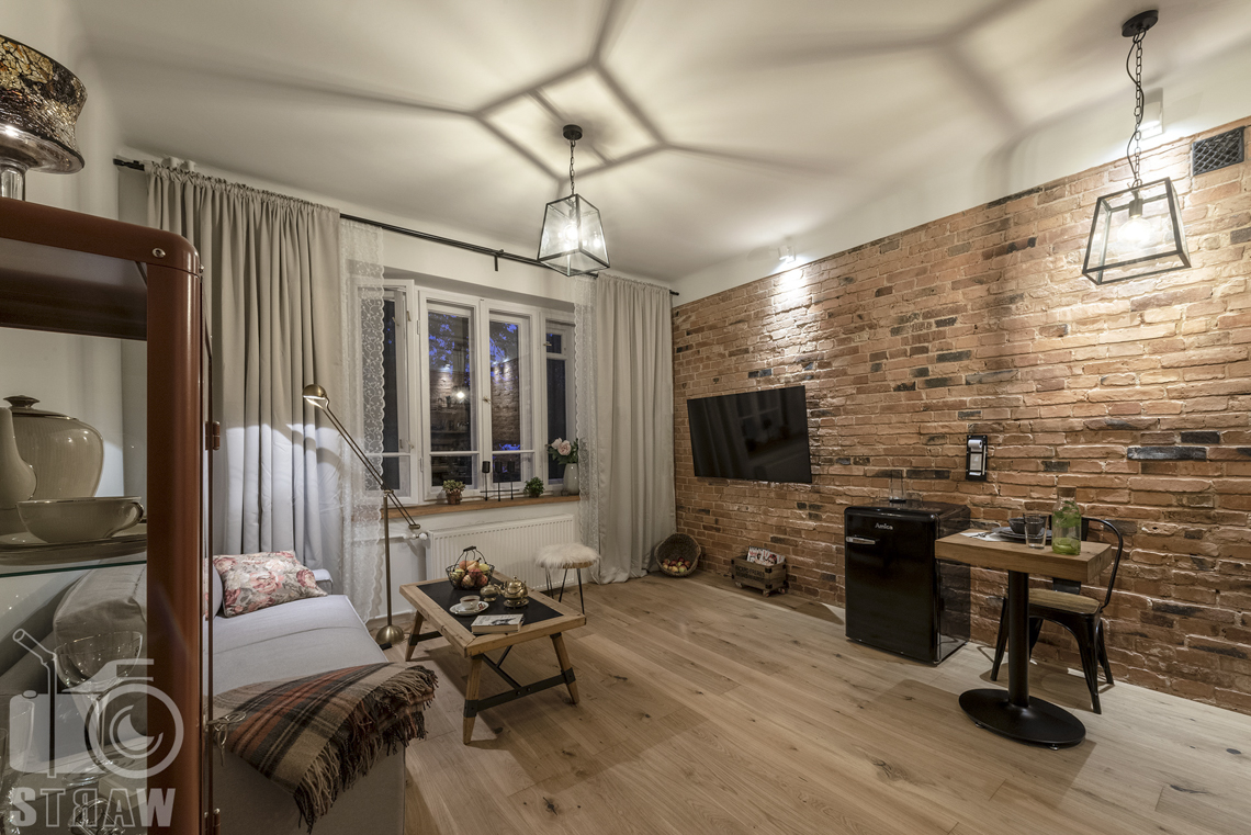 Fotografia booking, zdjęcia apartamentu, pokój wypoczynkowy, stół, telewizor, serwantka, stolik podręczny, krzesło.