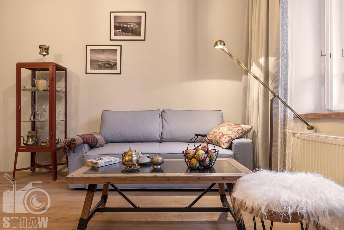 Fotografia booking, zdjęcia apartamentu, pokój wypoczynkowy, sofa, stół, na stole koszyk z owocami, imbryk, cukiernica, książka, obok stołek, lampka, obrazy na ścianie.