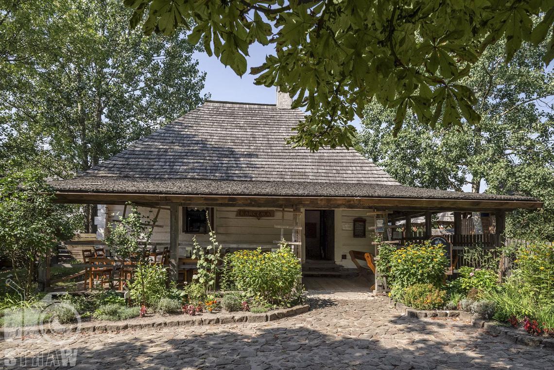 Fotografia architektury, zdjęcia budynków w skansenie wsi w Kielcach, chata wiejska z przedłużonym dachem tarasowym, wokół ogródek.