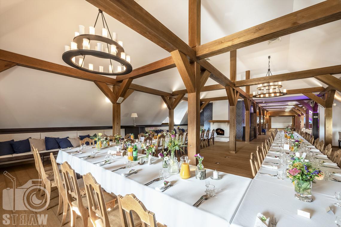 Zdjęcia karczmy, Kuźnia smaków, Kielce, restauracji, sali weselnej, Sala weselna kominkowa, Stół ustawiony w podkowę, w tle kominek, salę oświetlają dwa żyrandole.