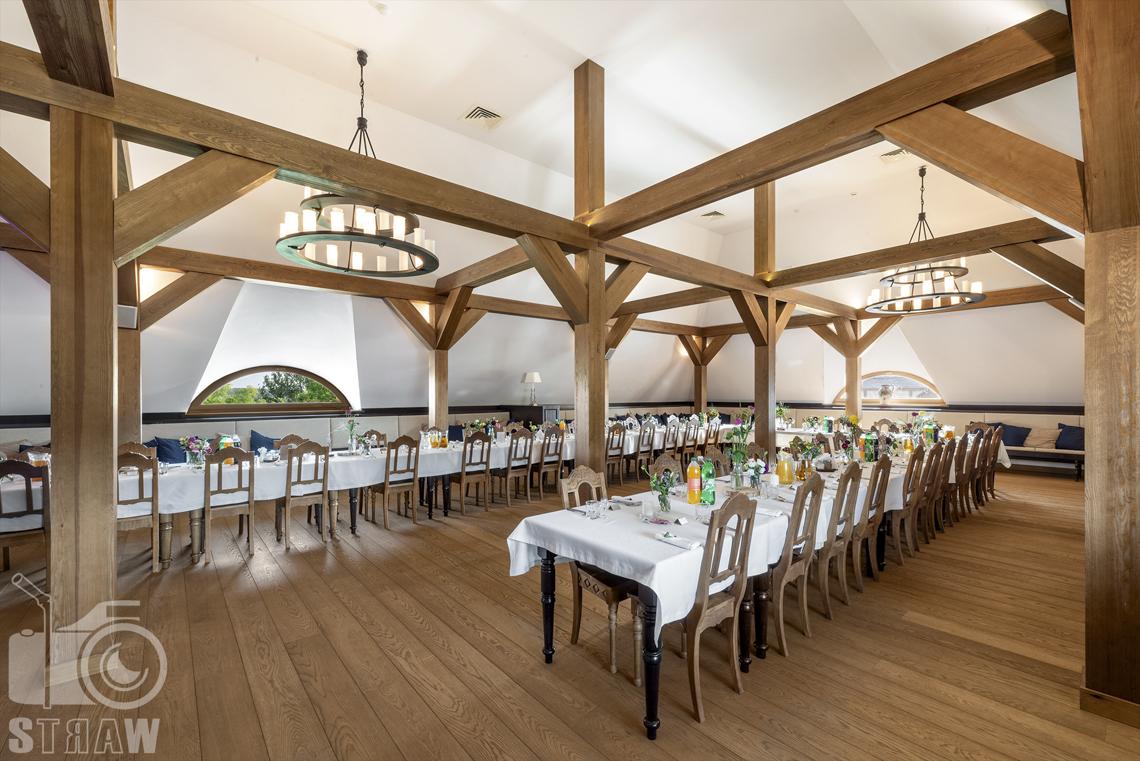 Zdjęcia karczmy, Kuźnia smaków, Kielce, restauracji, sali weselnej, Sala weselna kominkowa, Stoły ustawione w podkowę, z krzesłami obok siebie, widać dwa żyrandole.