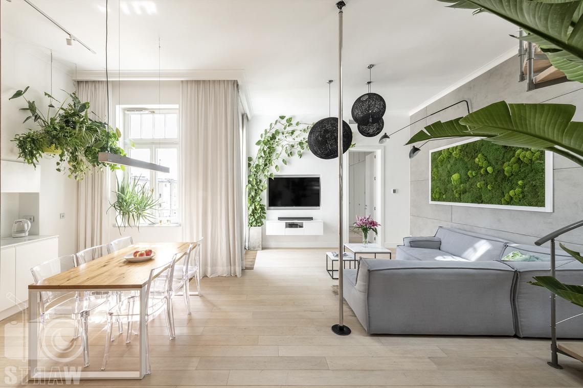 Zdjęcia mieszkania na sprzedaż w Warszawie, salon, kuchnia i jadalnia z dużym stołem, wiszące kwiaty i czarne koliste lampy.