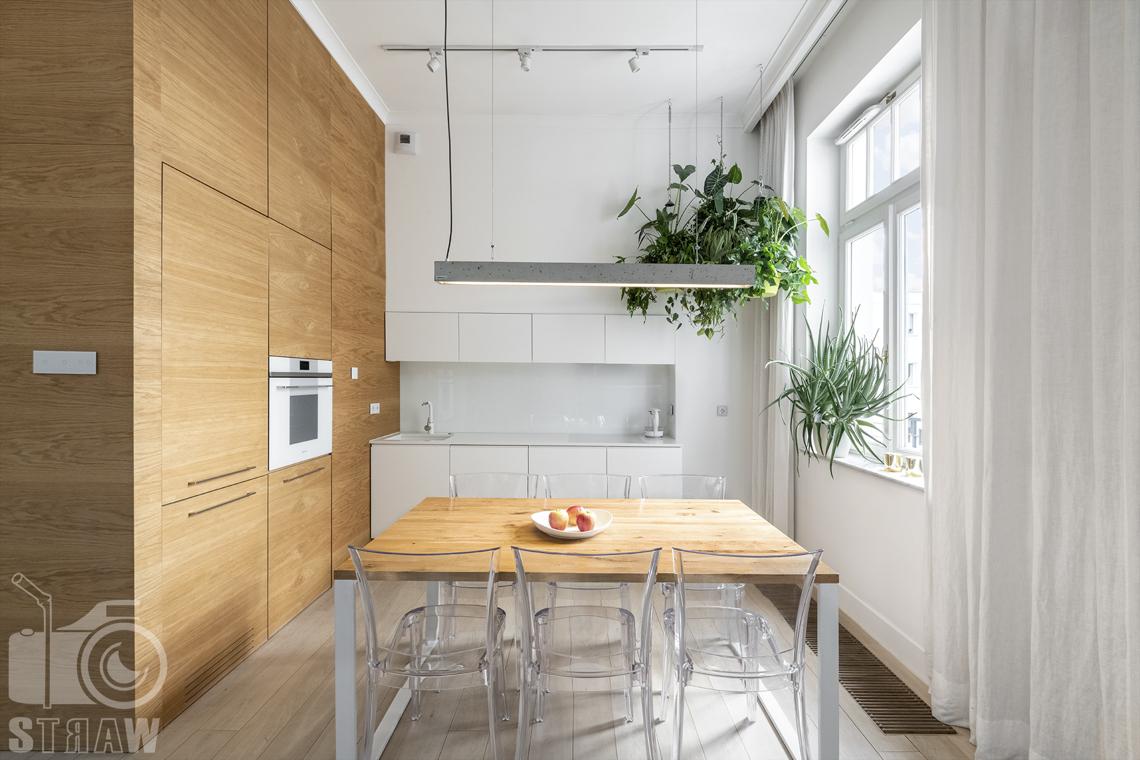 Zdjęcia mieszkania na sprzedaż w Warszawie, kuchnia, drewniany stół i zabudowa, betonowa lampa i wiszące kwiaty.