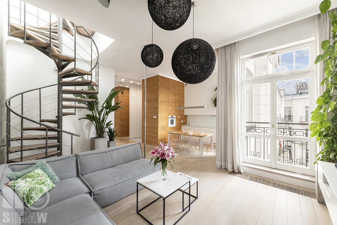 Zdjęcia mieszkania na sprzedaż w Warszawie, salon, okno, sofa i stolik kawowy z kwiatami.