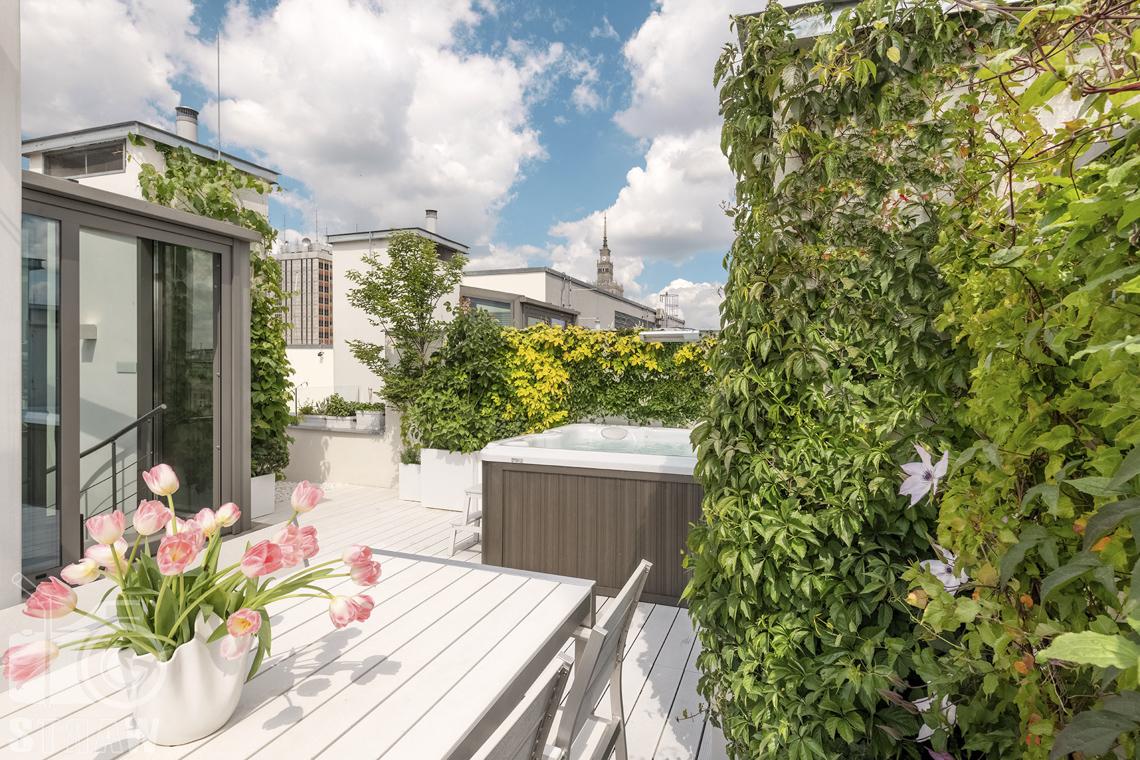 Zdjęcia mieszkania na sprzedaż w Warszawie, taras na dachu, stół, jacuzzi i widok na Pałac Kultury i Nauki.