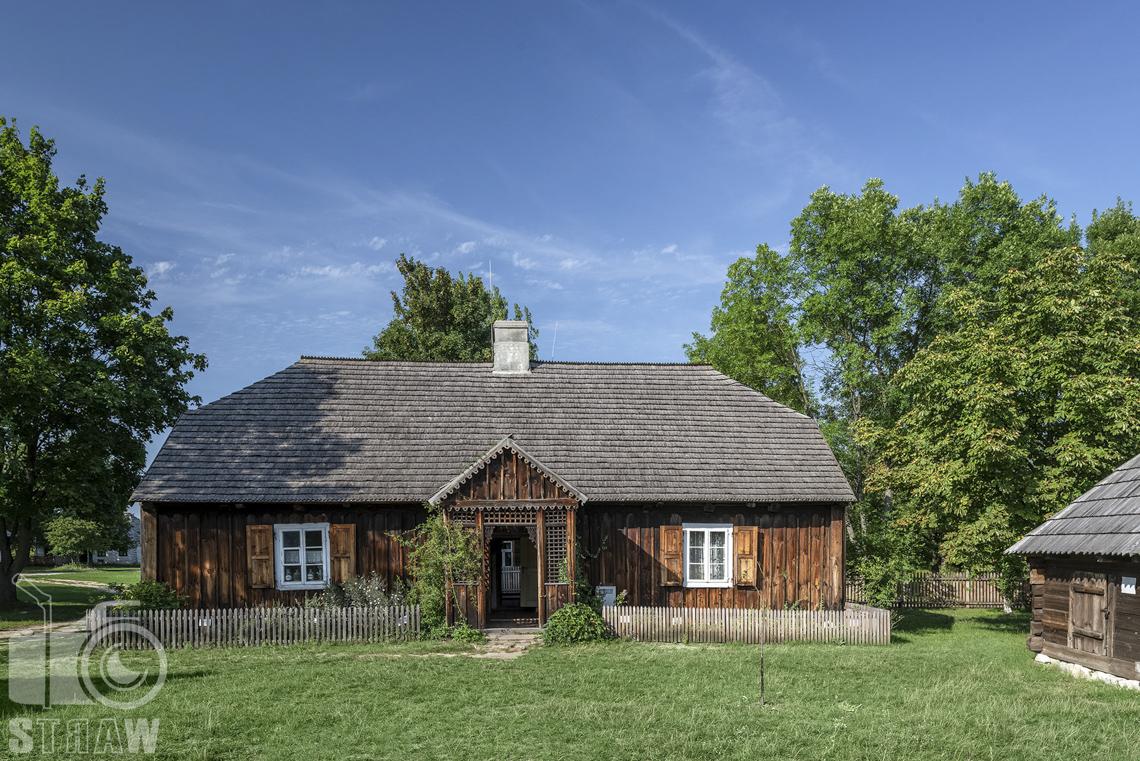 Fotografia architektury, zdjęcia budynków w skansenie wsi w Kielcach, drewniana chata wiejska z przydomowym ogródkiem.